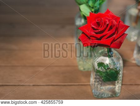 Scarlet Rose Bud In Decorative Bottle On A Wooden Background. Beatiful Rose In Vase With Copy Space.