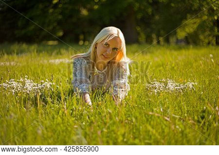 Peaceful Girl Lying On Green Grass With Stretched Arms And Legs. Blond Woman Lying On The Grass