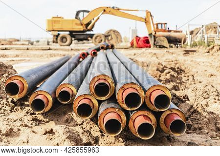 Hot Water And Heating Pipes With An Excavator In The Background. Cold And Hot Water, Heating And Hea