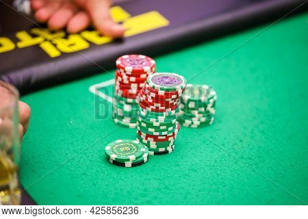 Minsk. Belarus - 25.06.2021 - Casino Chips On A Green Gambling Table. High Quality Photo