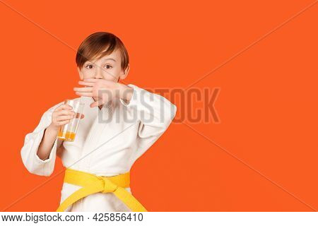 Boy In White Kimono Drinks Water. Kid Practicing Karate On Color Background. Kid Sport Concept.