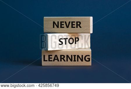 Never Stop Learning Symbol. Wooden Blocks With Concept Words Never Stop Learning. Beautiful Grey Bac