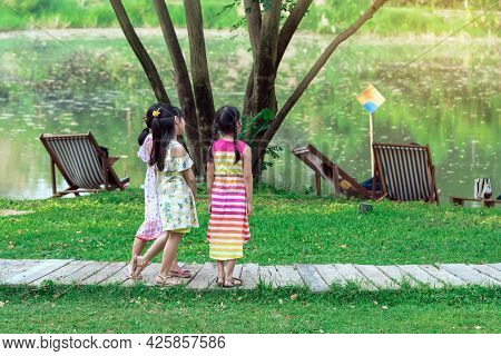 Asian Girls And Friends Playing Together On Pathway Through Green Garden. Happiness Girl Friends Hav