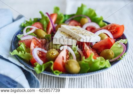 Greek Salad Of Fresh Vegetable With Tomatoes, Lettuce, Olives, Red Onion And Feta Cheese In Bowl On