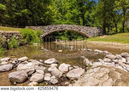 Stone Arch Bridge Over A Creek In The Woods