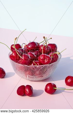 Close-up Of Fresh, Juicy, Organic Cherries In A Glass Bowl Against A Pink Pastel Background. Seasona