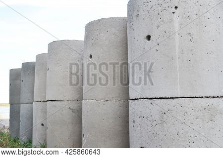Reinforced Concrete Rings Of Gray Color For The Construction Of Sewers And Wells, Outside They Stand
