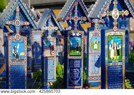 SAPANTA, ROMANIA - JUNE 08, 2021 - Painted blue wooden crosses in the Merry Cemetery in Maramures, an unique and amusing monument in the entire world