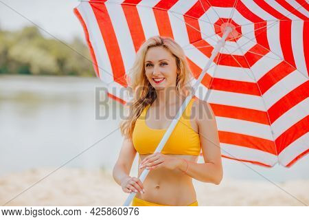 Young Attractive Blond Haired Woman In Yellow Summer Bikini Posing With Bir Red And White Stripped S