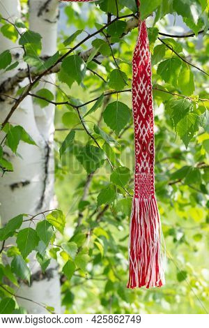 Red And White Ribbon With Ornament Of Traditional Slavic Signs Hanging On A Young Birch. Celebrating