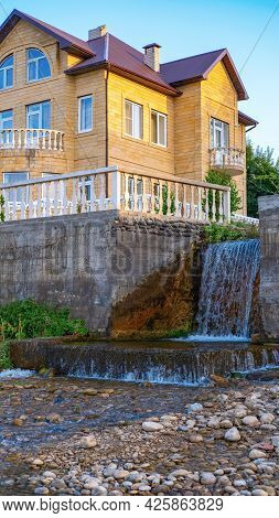 A Small, Beautiful Waterfall Flows Past Private Houses Into The Caspian Sea In Dagestan. Water Flows
