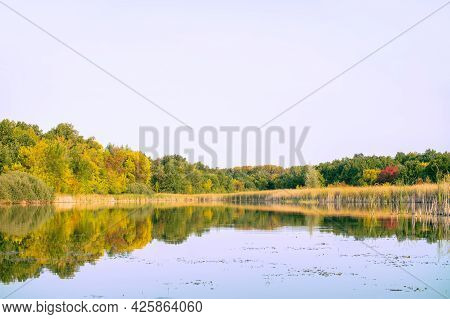 View Of The Autumn Forest With Yellow And Red Foliage And A Beautiful Lake Against The Background Of