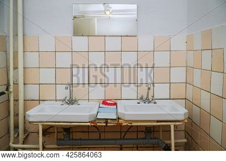 Bathroom Interior With White Sink And Faucet On Background Of Tiled Wall