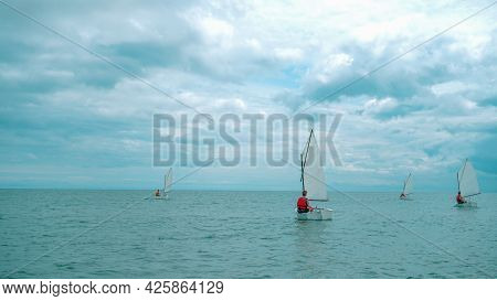 Young Men In The Sea Sail On Sailing Boats.