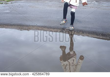 In A Large Puddle Is Reflected A Girl Who Put Her Foot Over A Puddle
