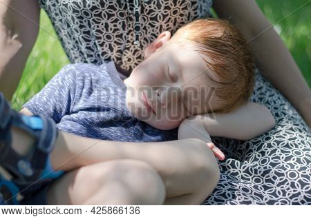 The Child Sleeps In The Open Air On The Lap Of The Mother. Children's Sleep In Nature. A Four-year-o