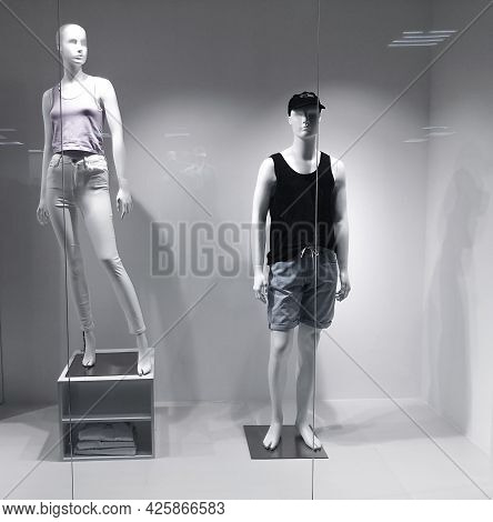Two Mannequins In A Shop Window Behind Glass. Man And Woman Mannequins Dressed In Clothes. Shop Mane