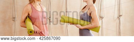 Cropped View Of Two Women Wearing Activewear Standing In Gym Holding Yoga Mat Ready To Start Fitness