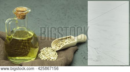 Sunflower Seeds And Oil And Background With Copy Space. Sunflower Seeds In A Wooden Spoon And Oil In