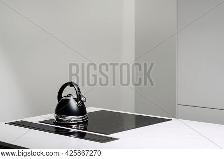 White Countertop With Small Black Kettle On Built In Electric Induction Stove Top And White Cubpboar