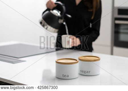 Woman In Dark Shirt Pouring Boiling Hot Water From Black Kettle Into Mug, About To Prepare Green Tea