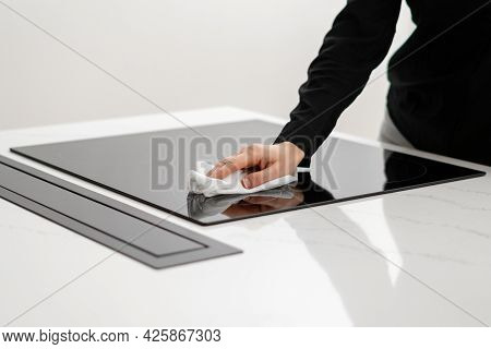 Woman Polishing Her Ceramic Induction Cooktop Built In Kitchen Appliances With Tissue, Using Special