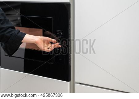 Cropped Shot Of Woman Turning Microwave Ovens Knob, Adjusting Time And Temperature Settings, Selecti