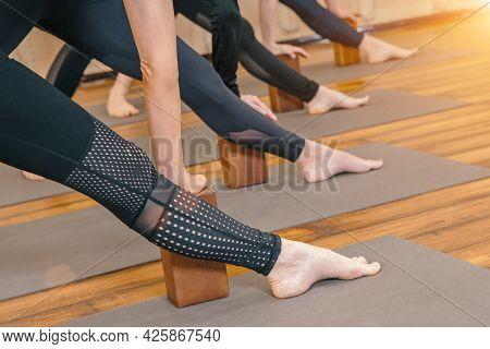 Cropped View Of Female Legs Doing Yoga Poses With Foam Yoga Blocks In Yoga Studio
