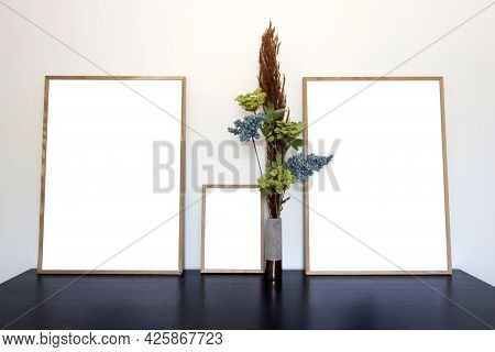 Three Canvas,picture Or Photo Frame For Copy Space Near White Wall On Wooden Table With Decorative H