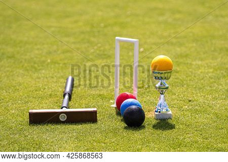 A Set Of Colored Balls, A Hammer And A Winners Prize At The Croquet Hoop On The Green Lawn