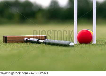 Croquet Mallet, Wicket And Colorful Balls On A Green Lawn