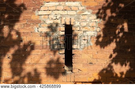 The Shadow Of The Tree Falls On The Stone Wall. On A Stone Wall Made Of Clay Stone A Shadow On A Sun