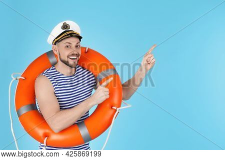 Happy Sailor With Orange Life Buoy Pointing On Light Blue Background, Space For Text