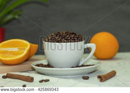 White Coffee Cup With Coffee Beans And Cinnamon Sticks. Beams Of Light Through The Blinds Illuminate