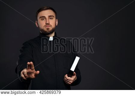Priest With Bible Making Blessing Gesture On Black Background. Space For Text