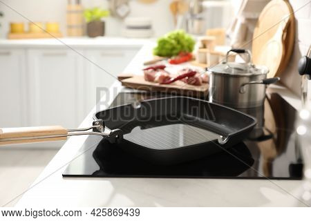 Frying Pan With Cooking Oil On Cooktop In Kitchen
