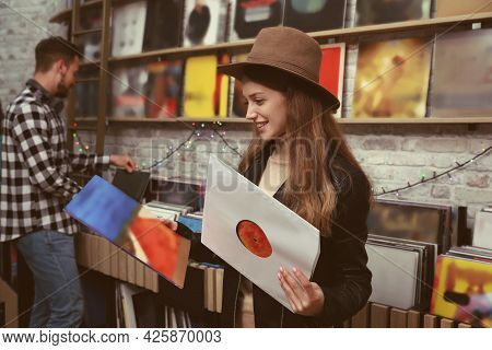 Young Woman With Vinyl Records In Store