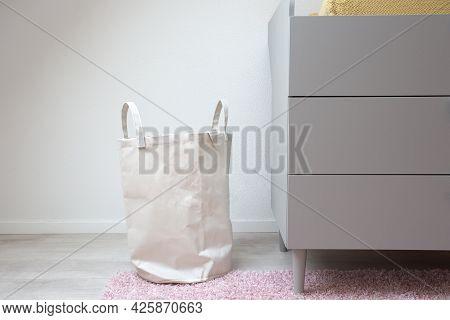 Stylish White Laundry Basket Standing In Modern Room, Modern Retro Scandinavian Decoration. New Home