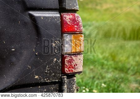 Stop Signal Taillight With Turn Signals Smeared With Swamp Close-up, Dirty Car Rear View On The Trun