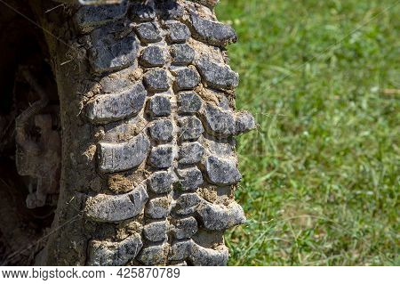 Car Tire With A Deep Tread For Off-road Driving Is Dirty In A Dry Swamp With A Clear Shot Against A