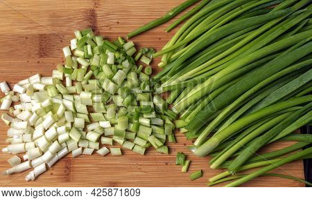 Top View Of Chopped Green Spring Onions On Wooden Board.