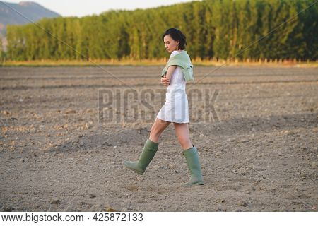 Asian Woman, Walking In The Countryside, Wearing A White Dress And Green Wellies.