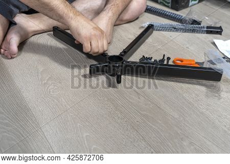 The Man's Hands Assembles The Crosspiece Of The Office Chair