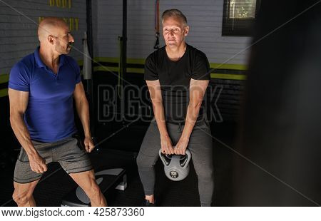 Male Personal Trainer Assisting Mature Man In Doing Kettlebell Swing Exercise In Home Gym