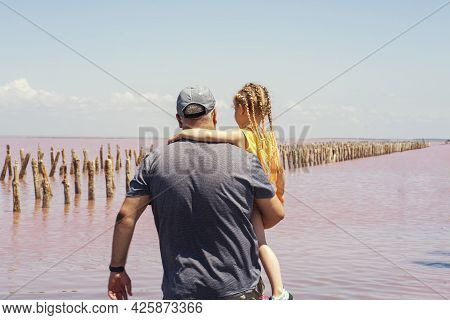 Dad And Little Daughter Admire The Pink Lake. Natural Miracle.