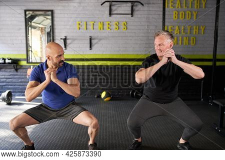 Male Personal Trainer Motivating And Supporting Elderly Senior Man While Doing Squats, Dynamic Movem