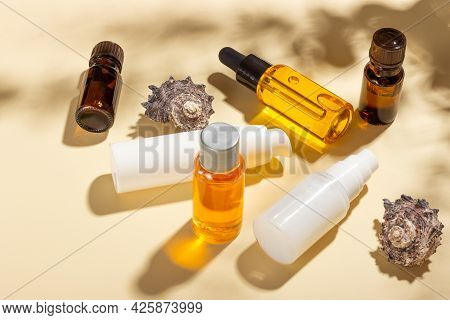 Tanning Oil. A Set Of Cosmetics Next To Seashells In The Sunbeams On A Pink Background. Cosmetics Fo