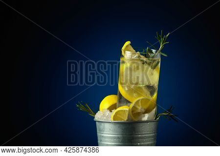 Gin-tonic Cocktail With Ice, Lemon, And Rosemary In A Metal Bucket With Ice.