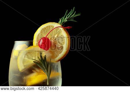 Cocktail Gin-tonic With Lemon Slices And Rosemary Garnished With A Preserved Cherry.