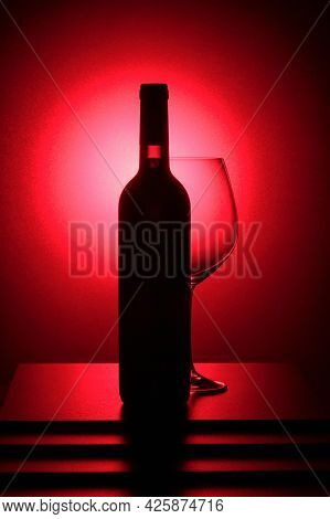 Bottle Of Red Wine And An Empty Glass. Red Backlight.